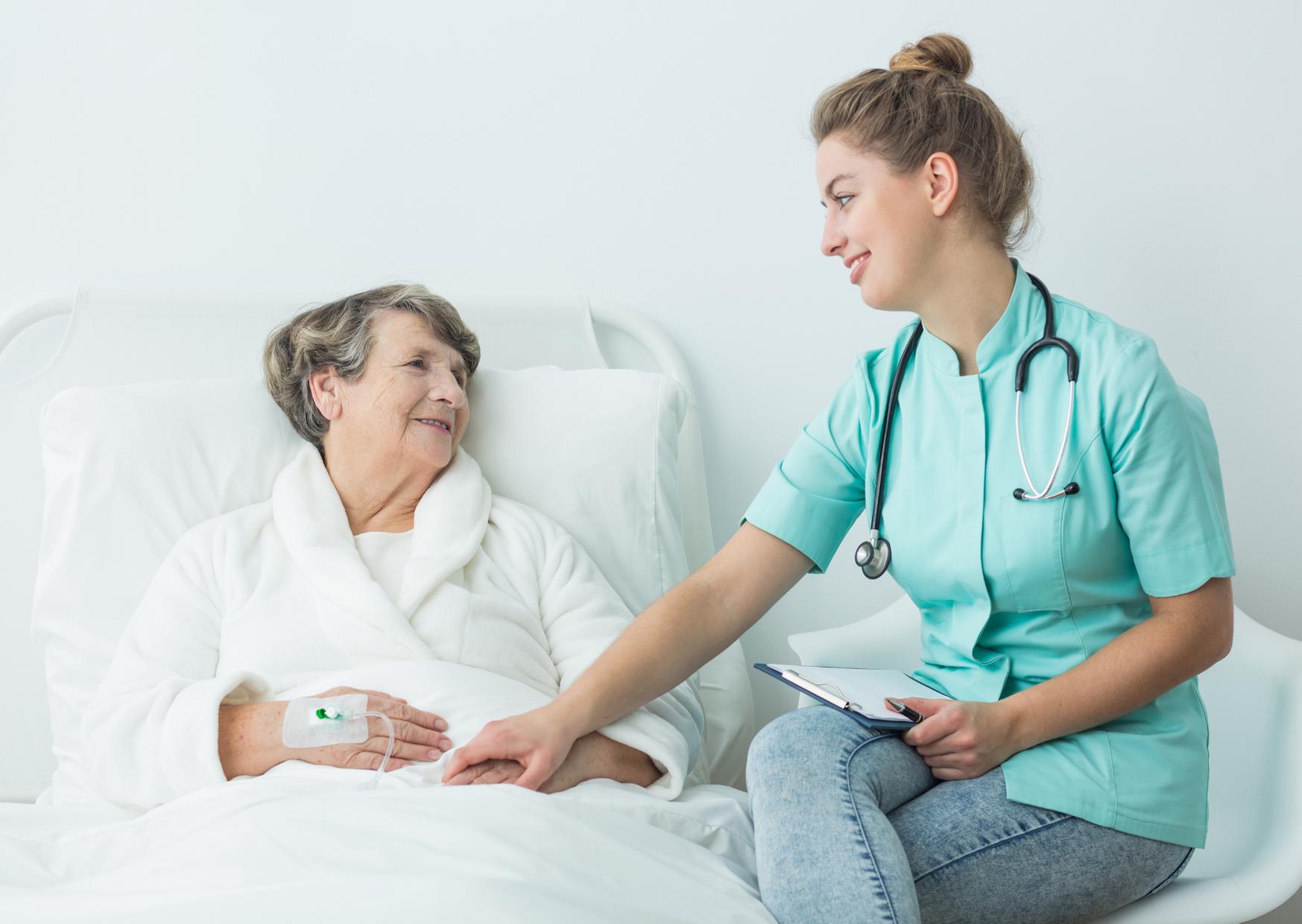 pielęgniarka trzymająca pacjentkę za rękę